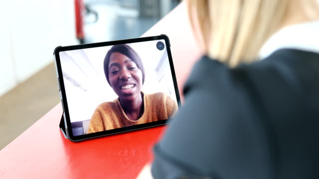 Business women making a video call Young african woman seen in the digital tablet screen during a video call.  Female sitting at office making video call using tablet PC. zoom call stock videos & royalty-free footage
