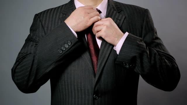 Businessman adjusting his necktie and jacket, close-up. Stylish men's wear video