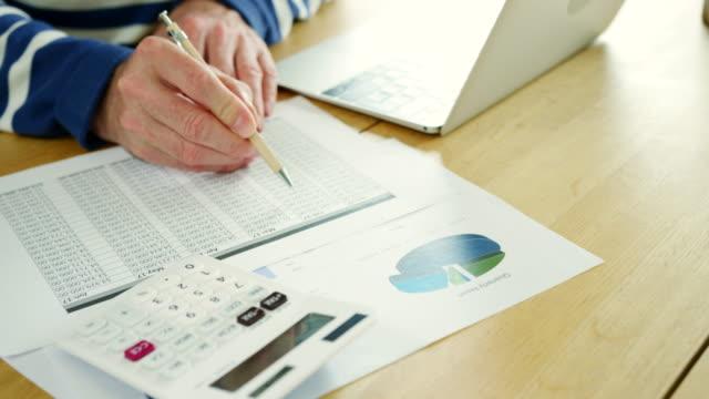businessman analysing and calculation financial data at his desk - długi filmów i materiałów b-roll