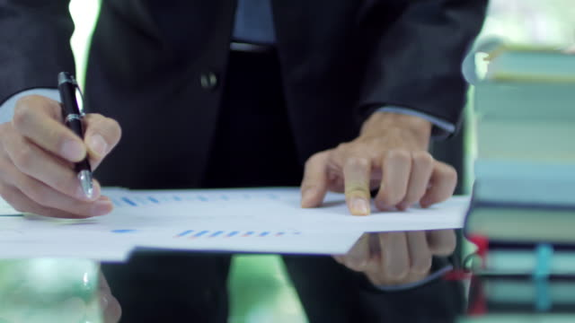businessman analyzing and checking document graph , dolly shot left to right - paragone video stock e b–roll