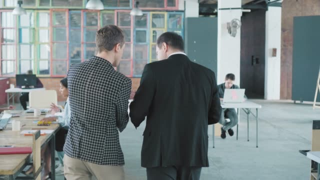 A businessman and a hired manager enter the office and go to the table where their colleagues are waiting for them. They greet the staff and start meet up. Office life. Co-working team. Back view video