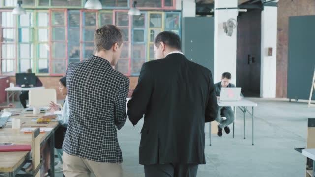 Ein Geschäftsmann und ein Angestellter betreten das Büro und gehen an den Tisch, wo ihre Kollegen auf sie warten. Sie begrüßen die Mitarbeiter und beginnen sich zu treffen. Büroleben. Co-Working-Team. Rückansicht – Video