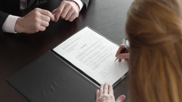 businessman and businesswoman signing a contract and shaking hands - contratto video stock e b–roll