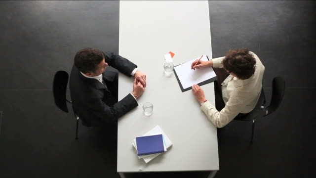 businessman and businesswoman sit towards at desk. Directly Above. video