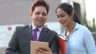 istock Businessman and businesswoman using digital tablet outside office building 1254047114