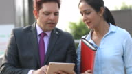 istock Businessman and businesswoman using digital tablet outside office building 1254050342