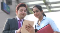 istock Businessman and businesswoman using digital tablet outside office building 1254057573