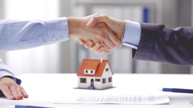 businessman and businesswoman with house model signing document and shaking hands at office