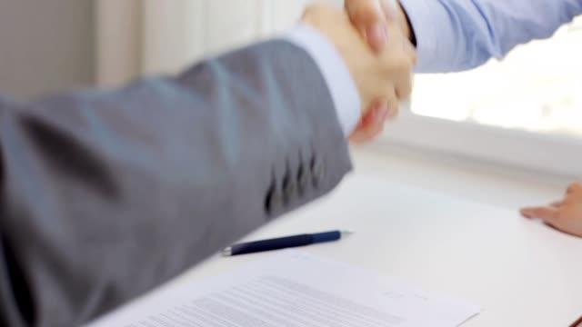 empresário e empresária com modelo de casa, assinar o documento e agitando as mãos no escritório - vídeo