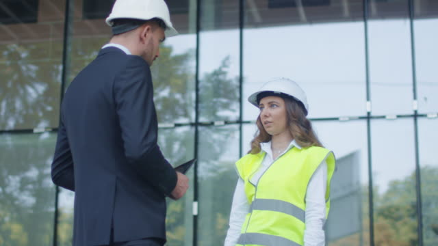businessman and female engineer in hard hats having agreement handshake on construction site. - костюм в комплекте стоковые видео и кадры b-roll