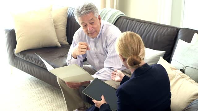 vídeos de stock e filmes b-roll de businessman and woman having discussion - senior business woman tablet