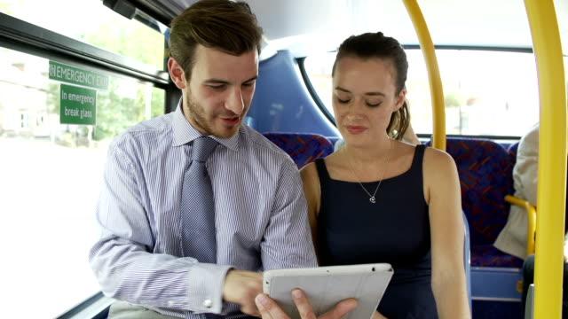 vídeos de stock e filmes b-roll de empresário e mulher usando tablet digital no autocarro - senior business woman tablet