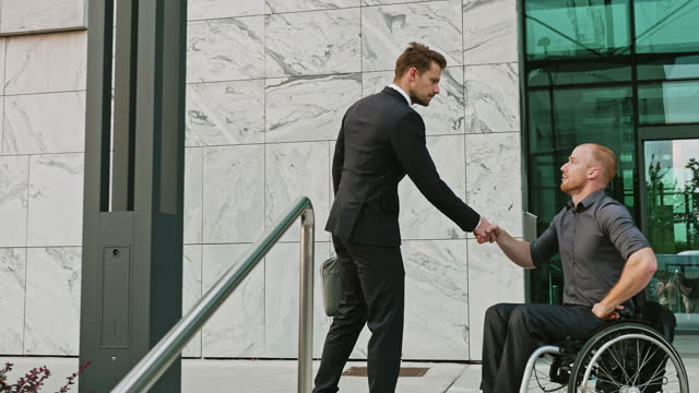 Businessman Approaching Disable Businessman on Wheelchair and Shaking Hands Outdoors