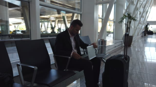 vídeos de stock, filmes e b-roll de homem de negócios em um aeroporto. - mobile