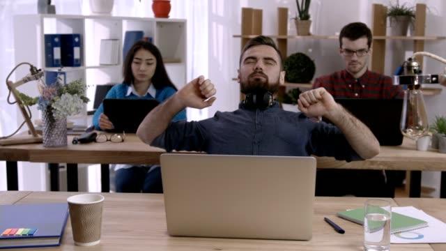 biznesmen przy biurku wyciągając ręce w biurze - rozciągać filmów i materiałów b-roll