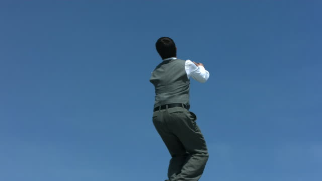 Businessman back flipping in sky, slow motion video