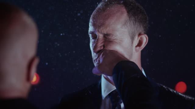 slo mo ld businessman being hit in the face in rain - colpire con un pugno video stock e b–roll