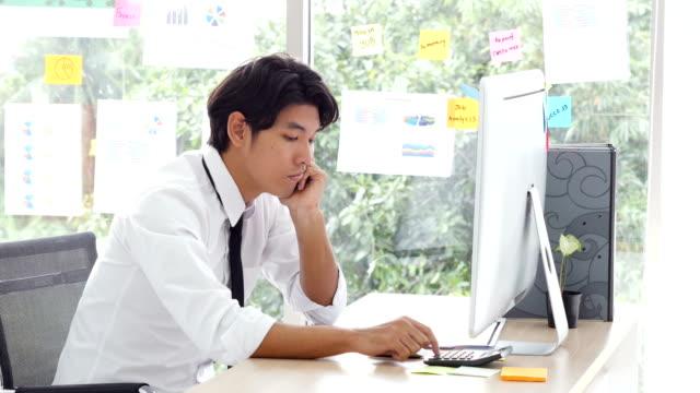 退屈なときに彼はオフィスで働くビジネスマン。彼の机で目を覚まし滞在する退屈アジア男性事務労働者の闘争。 ビデオ