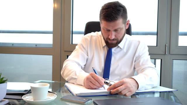 Businessman browsing documents, making notes, office, portrait, slider shot video