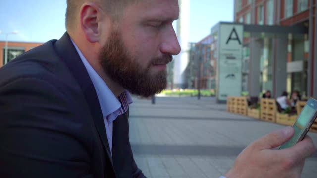 Businessman browsing smartphone. Close and tilt shot, steadicam.