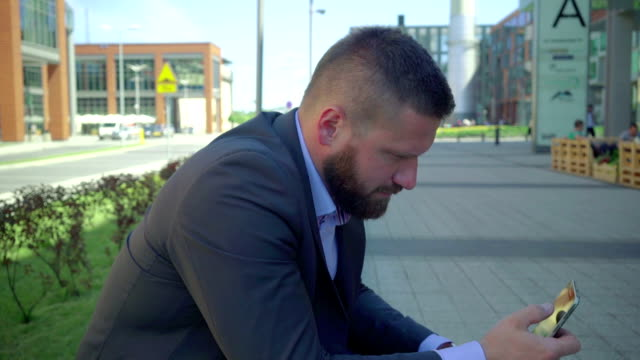 Businessman browsing smartphone, close shot, tilt shot.