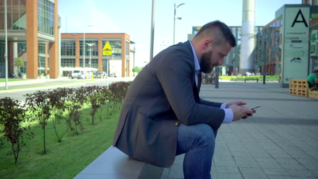 Businessman browsing smartphone.