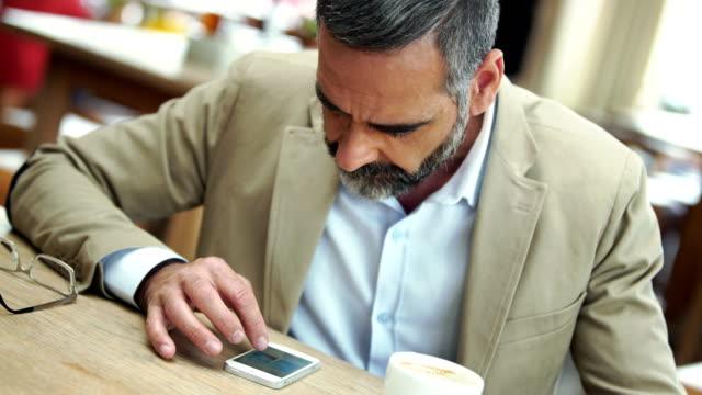 Empresario de navegación web en su teléfono inteligente. - vídeo