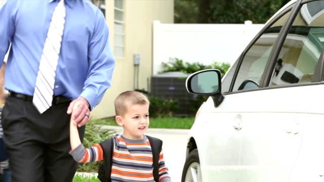 businessman carrying baby taking boys to school - odejście filmów i materiałów b-roll