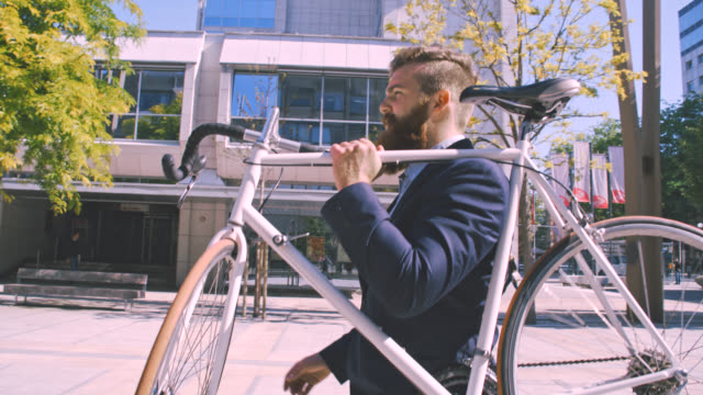ms businessman carrying his bicycle down the street - hipster stock videos and b-roll footage
