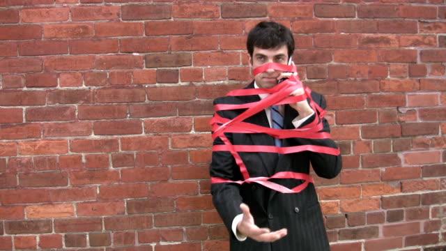 vidéos et rushes de homme d'affaires surpris par la paperasserie. - ligoté