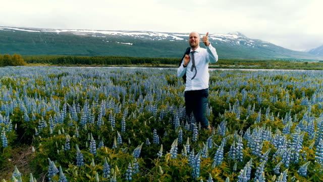 stockvideo's en b-roll-footage met zakenman vieren van succes op een weide vol bloemen - er even tussenuit