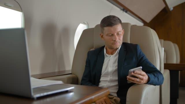 Empresario hablando sentado en cómodo sillón en cabina de avión privado - vídeo