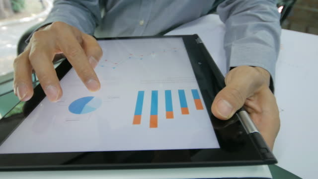 Businessman checking and analyzing graph on digital tablet , dolly shot right to left video