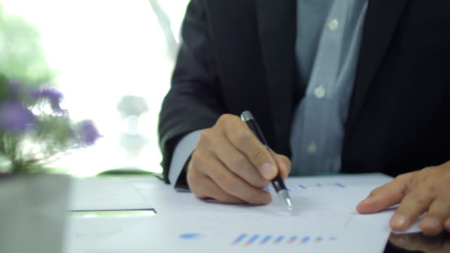 Businessman checking and analyzing graph on working space at office video
