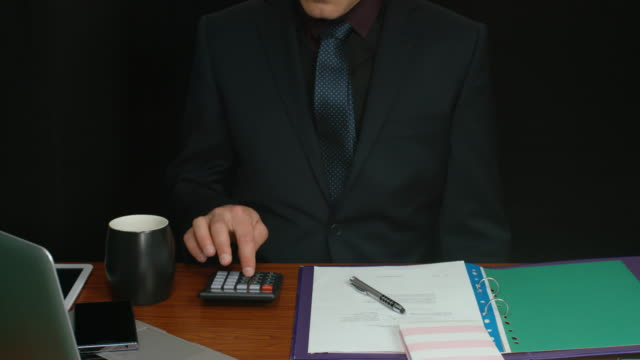 Businessman Checking Documents And Performing Calculations In Office video