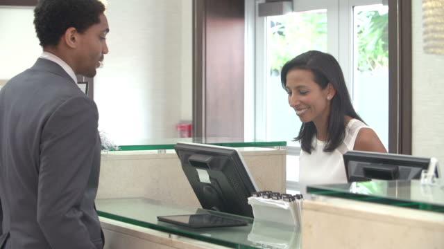Ejecutivo de realizar el check-In en la recepción del Hotel la recepción - vídeo
