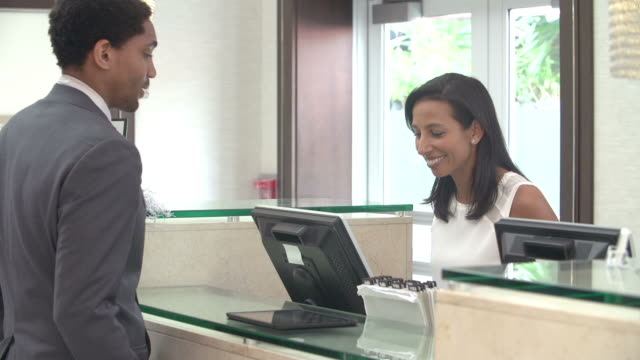 businessman checking in at hotel reception front desk - hotel reception stok videoları ve detay görüntü çekimi