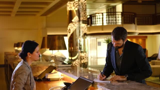 affärsman checkar in på hotellet. ung stilig man och receptionist i diskreception. näringsidkare fyller i informationsformulär i receptionen - framifrån bildbanksvideor och videomaterial från bakom kulisserna