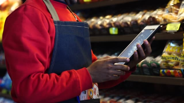 Businessman checking inventory in a digital tablet at a supermarket