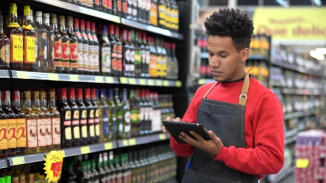 businessman checking inventory in a digital tablet at a supermarket - retail worker stock videos and b-roll footage