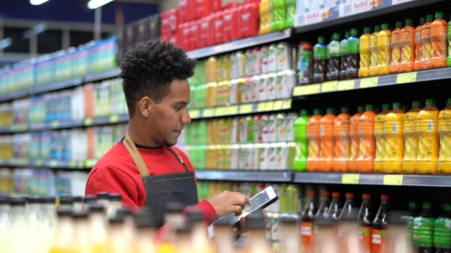 businessman checking inventory in a digital tablet at a supermarket - retail worker stock videos & royalty-free footage