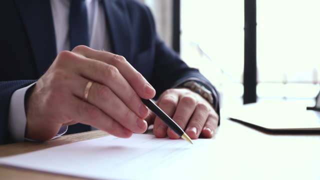 Businessman checking, signing legal document concept, close up view Businessman checking, signing legal document concept. Executive wearing suit reading financial contract, writing signature on official paper. Male hand holding pen doing paperwork, close up view form filling stock videos & royalty-free footage