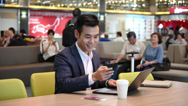 Businessman checking text message and working on laptop at airport