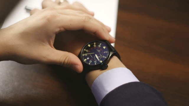 Businessman checking wrist watch. The watch on the hand video