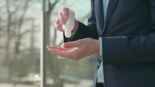 Affärsman rengöring händerna med flytande sanitiser gel video