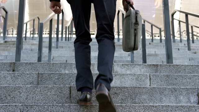 Businessman climbs stairs to bank office - vídeo