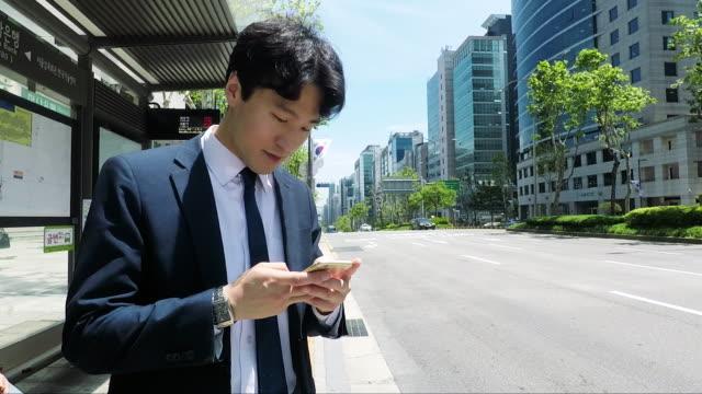 stockvideo's en b-roll-footage met zakenman woon-werkverkeer met de bus in seoel - zuid-korea - bushalte