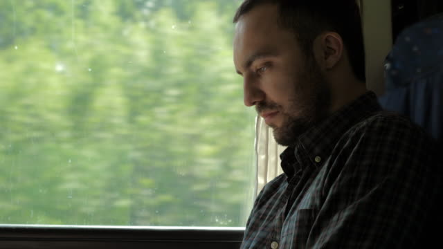Businessman Commuting On Train Using Digital Tablet