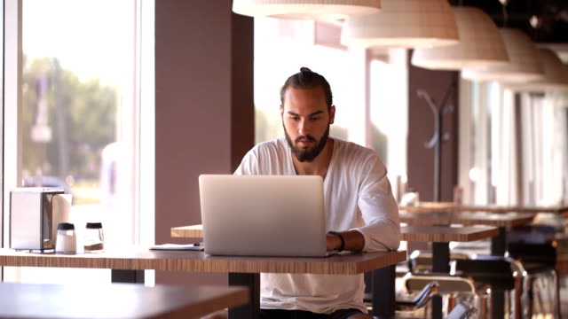 businessman connecting to wireless on his laptop computer in modern interior video