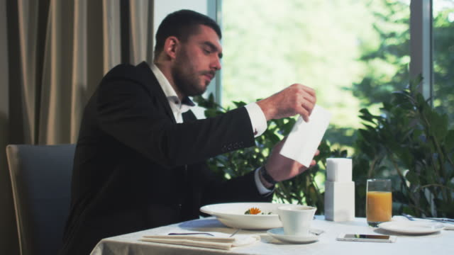 Businessman coughs and uses a tissue in a restaurant. video